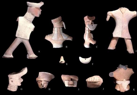 Figurinas de guerreros, que muestran una variada vestimenta, como taparrabo (k), faldellín (B, C), y camiseta (A, d); ornamentos como gorro (A, B, C, G, h, i), nariguera (A, B, C, F, G, h, i), collar (A, B, C, G) y pintura facial (A, i). Portan además instrumentos musicales, como pututo (J), y sonaja (e)